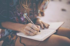 Boho girl writing in her diary wearing a floral dress